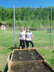 4-Hers standing by their raised bed garden project