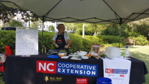 FCS Agent stands beneath a tent while providing a local food preparation demonstration