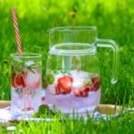 glass and pitcher of infused water with strawberries and mint on grass